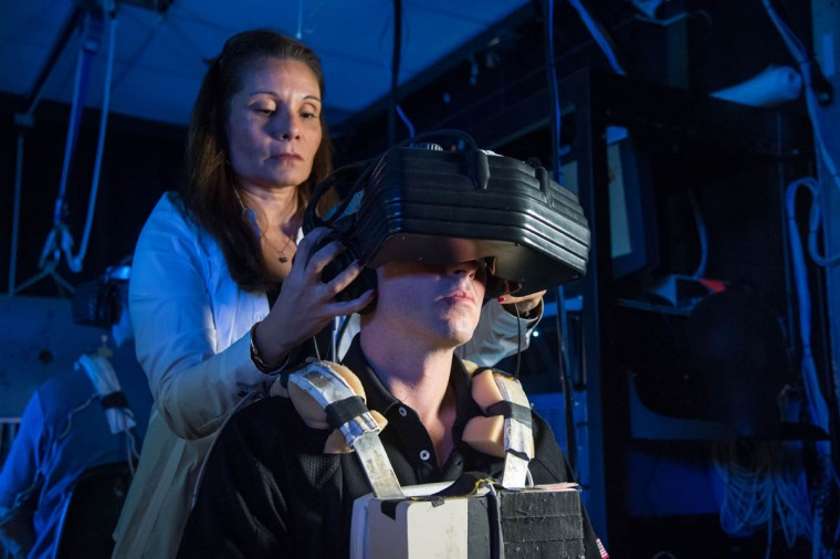 NASA astronaut Reid Wiseman, Expedition 40/41 flight engineer, uses virtual reality hardware in the Space Vehicle Mock-up Facility at NASA's Johnson Space Center to rehearse some of his duties on the upcoming mission to the International Space Station. This type of virtual reality training allows the astronauts to wear a helmet and special gloves while looking at computer displays simulating actual movements around the various locations on the station hardware with which they will be working. (NASA)