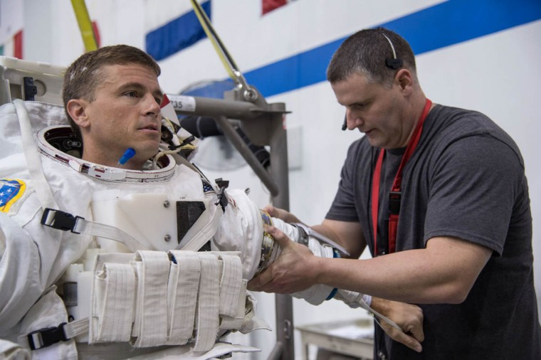 NASA astronaut Reid Wiseman, Expedition 40/41 flight engineer, gets help donning a training version of his Extravehicular Mobility Unit (EMU) spacesuit in preparation for a spacewalk training session in the waters of the Neutral Buoyancy Laboratory (NBL) near NASA's Johnson Space Center. (NASA)