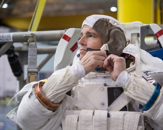 NASA astronaut Reid Wiseman, Expedition 40/41 flight engineer, dons a training version of his Extravehicular Mobility Unit (EMU) spacesuit in preparation for a spacewalk training session in the waters of the Neutral Buoyancy Laboratory (NBL) near NASA's Johnson Space Center. (NASA)