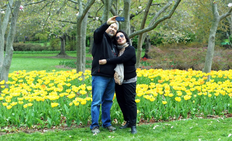 Thanavat Junchaya photographs himself and his wife, Penporn Junchaya, in Sherwood Gardens among the trees and tulip beds. They live in Falls Church, Va., and have traveled to many areas in the region to see spring flowers and flowering trees. (Kim Hairston/Baltimore Sun)