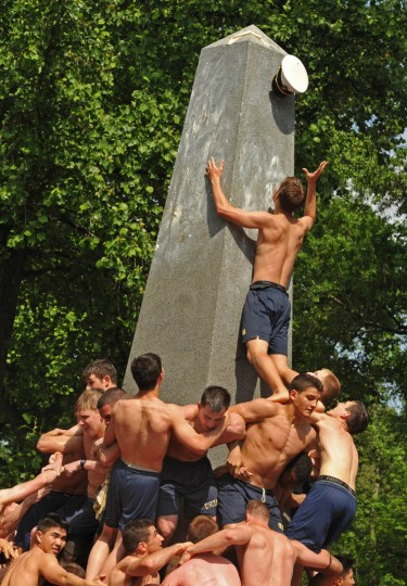 One of the valiant but failed attempts to replace the dixie cup with an upperclassman's hat. The Herndon Monument Climb, the culmination of plebe year at the U.S. Naval Academy, was completed in 2:19:35 this year. (Amy Davis Baltimore Sun)