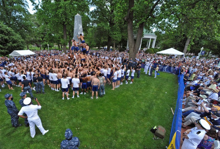 The tradition of adding the slippery vegetable shortening to make the Herndon Monument Climb more difficult began in 1950. Midshipmen of the 1st Company apply about 50 pounds. (Amy Davis Baltimore Sun)