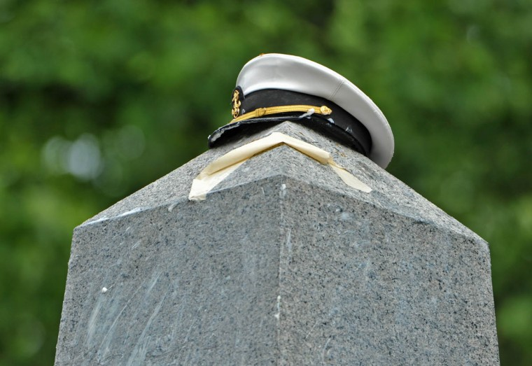 """The Herndon Monument Climb ends when the plebes successfully place a midshipman's cover atop the monument, named for Commander William Lewis Herndon, who went down with his ship in a hurricane in 1857. The tape is left from the """"dixie cup"""" hat which was already removed by the plebes. (Amy Davis Baltimore Sun)"""