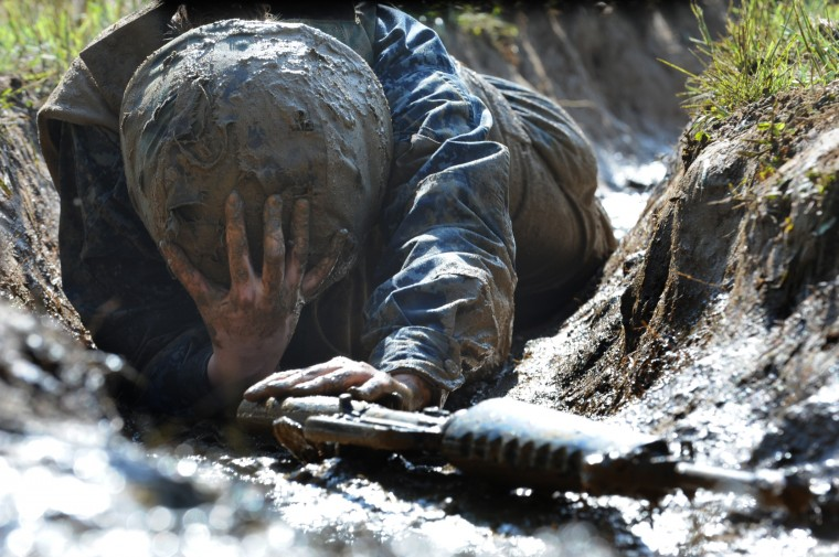 Midshipman Molly McAuliffe from Wichita, Kansas holds on to her helmet as she crawls through a trench. The United States Navy held its Sea Trials today, a 14-hour Navy and Marine Corps-related team challenge that includes water tactics, an obstacle course, a two-mile run, pugil stick jousting, and several other survival skills. (Photo by Algerina Perna/Baltimore Sun)