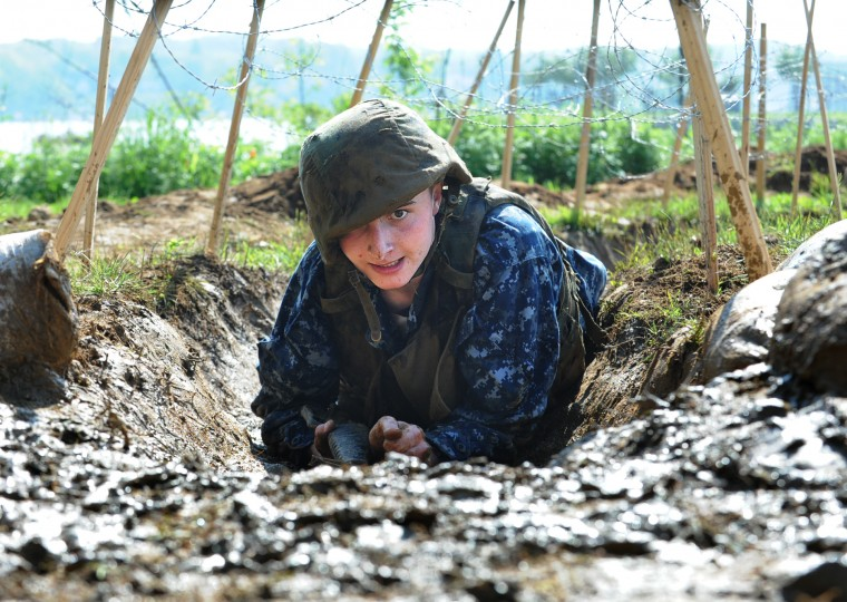Midshipman Justin Reed from Bentonville, Arkansas, moves through the trench covered with barbed wire. The United States Navy held its Sea Trials today, a 14-hour Navy and Marine Corps-related team challenge that includes water tactics, an obstacle course, a two-mile run, pugil stick jousting, and several other survival skills. (Photo by Algerina Perna/Baltimore Sun)