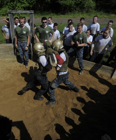 Midshipmen watch as fellow plebes Jules Murphy, left and Liam Cator joust with pugil sticks. The United States Navy held its Sea Trials today, a 14-hour Navy and Marine Corps-related team challenge that includes water tactics, an obstacle course, a two-mile run, pugil stick jousting, and several other survival skills. (Photo by Algerina Perna/Baltimore Sun)