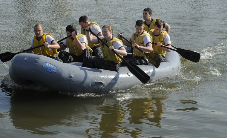 """Midshipmen row the Zodiac raft as part of the """"Wet and Sandy"""" section of the Sea Trials. The United States Navy held its Sea Trials today, a 14-hour Navy and Marine Corps-related team challenge that includes water tactics, an obstacle course, a two-mile run, pugil stick jousting, and several other survival skills. (Photo by Algerina Perna/Baltimore Sun)"""