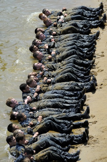 """With linked arms, plebes do push-ups in the water as part of the """"Wet and Sandy"""" exercises. The United States Navy held its Sea Trials today, a 14-hour Navy and Marine Corps-related team challenge that includes water tactics, an obstacle course, a two-mile run, pugil stick jousting, and several other survival skills. (Photo by Algerina Perna/Baltimore Sun)"""
