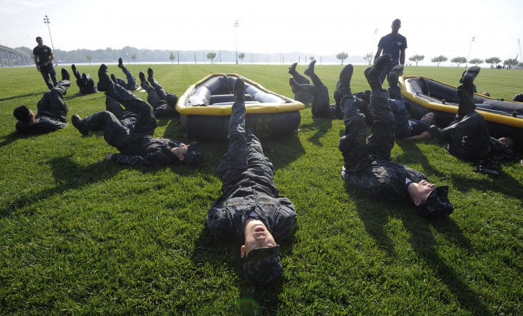 Shawn Park from New York, NY, center, and his fellow plebes exercise by zodiacs. The United States Navy held its Sea Trials today, a 14-hour Navy and Marine Corps-related team challenge that includes water tactics, an obstacle course, a two-mile run, pugil stick jousting, and several other survival skills. (Photo by Algerina Perna/Baltimore Sun)