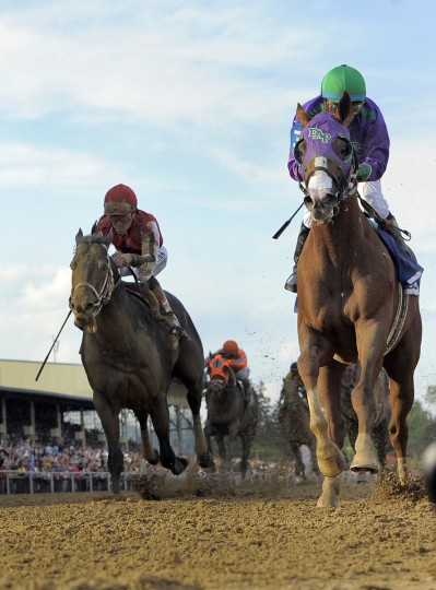 California Chrome crosses the finish line winning by a length and a half at the Preakness Stakes. (Kenneth K. Lam and Karl Merton Ferron/Baltimore Sun)