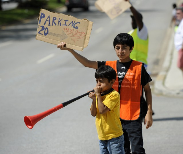 Edward Ortega, 8, blows a vuvuzela while his brother Alexander, 13, holds a parking sign on Northern Parkway prior to the Preakness. (Jerry Jackson/Baltimore Sun)