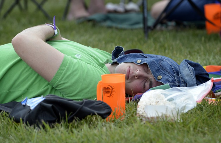 A racegoer takes a nap in the infield before the running of the 139th Preakness Stakes at Pimlico Race Course. (Lloyd Fox/Baltimore Sun)