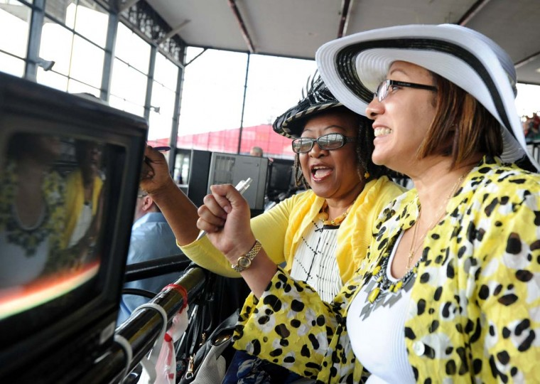 Pearl Ribeiro-Ayeh, left, and Kernovia Holomah cheer from the main grandstand as their horse wins in the 2nd race at Pimlico Race Course on Preakness Saturday. ( Robert K. Hamilton/Baltimore Sun)