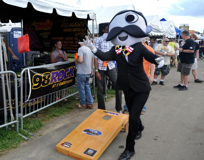 Mr. Boh tries his hand at cornhole in the Preakness infield. (Robert K. Hamilton/Baltimore Sun)