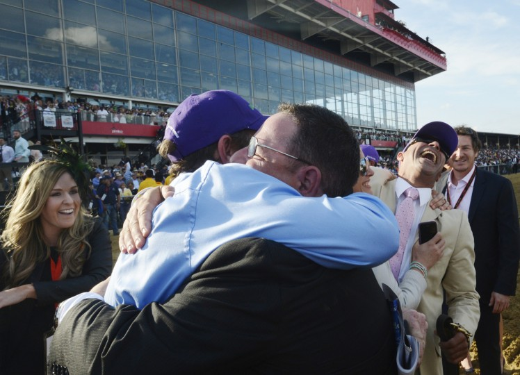 Assistant trainer Alan Sherman is jubilant after his horse, California Chrome, wins the 139th Preakness Race at Pimlico. In the background in the purple hat is exercise rider Willie Delgado. (Kim Hairston/Baltimore Sun)