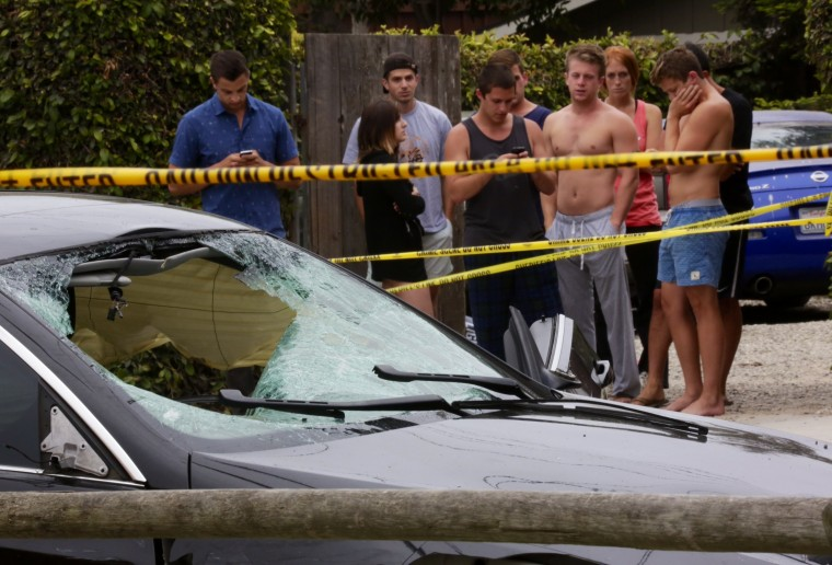 People gather near shooting scene in Isla Vista where seven people were killed and 7 people wounded in a shooting spree Friday night in the college town around UCSB.The black BMW is foreground is believed to be the shooters car. (Irfan Khan / Los Angeles Times)
