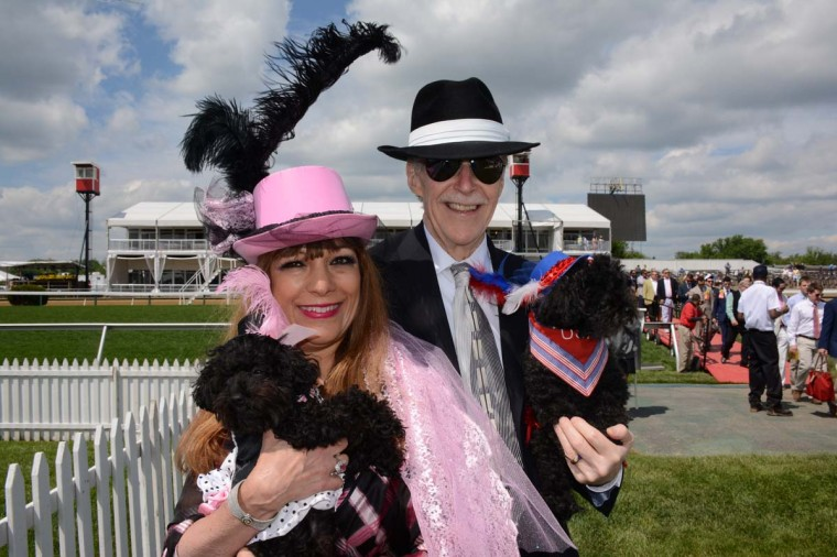 "Carol Huff, 58, and husband Lawrence Huff, 74 – partners in a real estate tenant business in Philadelphia – got special permission to bring their toy poodles with them to the Preakness corporate village. Carol Huff dressed to match Tiffany, 15-months-old, while Lawrence Huff described the look on Karizma, 10-years-old, as ""American princess."" (Sloane Brown/For the Baltimore Sun)"
