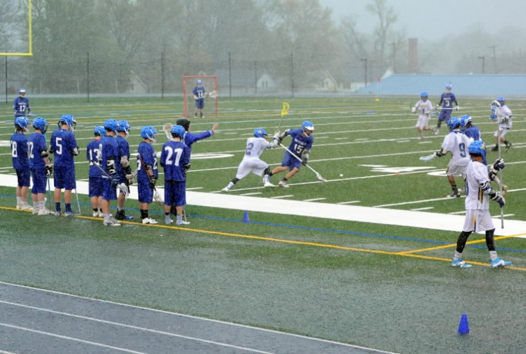 The Aberdeen and North East varsity boys lacrosse teams battle each other and the downpour of rain Wednesday, April 30 at Aberdeen High School. Play was stopped twice in the game as lightning strikes were spotted in the area. (Matt Button/BSMG)