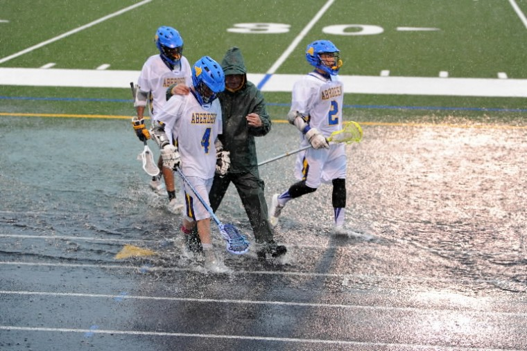 Members of the Aberdeen varsity boys lacrosse team make their through large puddles along the field during Wednesday's game against North East at Aberdeen. Play was stopped twice because of lightning in the area. (Matt Button/BSMG)