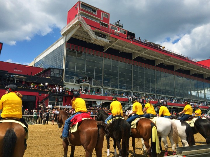 Pimlico track riders with their horses line the track opposite the grandstands on Preakness Day. (Robert K. Hamilton/Baltimore Sun)