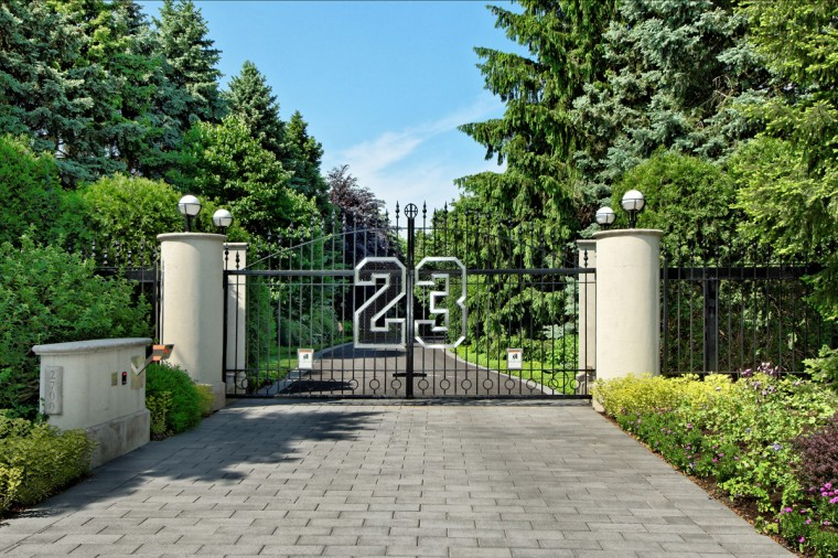 The front gate bearing Michael Jordan's jersey number 23 leads down a long driveway to his home. (JS Eckert Photography)