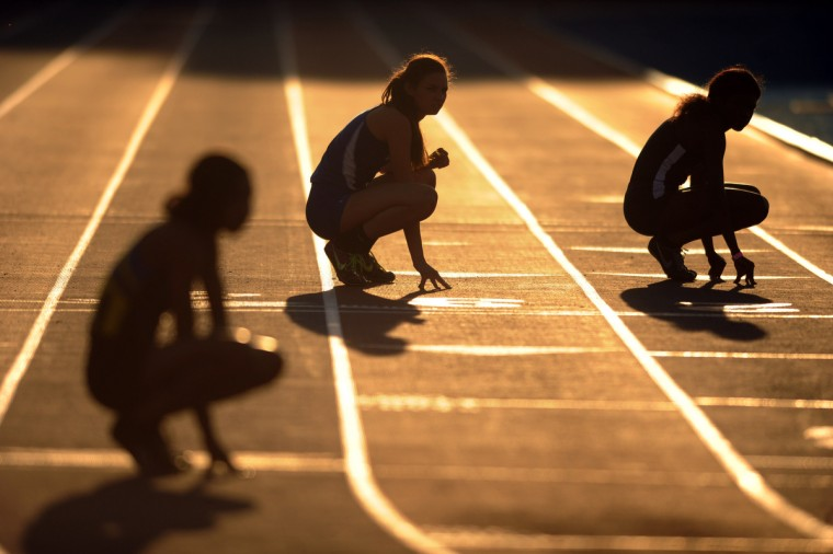 Relay runners are silhouetted in late afternoon light as they crouch during the 2014 track and field state championships at Morgan State University. (Brian Krista/BSMG)