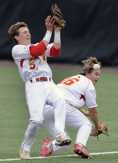 Calvert Hall second baseman Tyler Webster, left, drops a foul ball hit by a Mount St. Joseph batter after colliding first baseman Andrew Kilcoyne in the second inning. (Steve Ruark/For BSMG)
