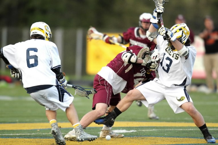 Catonsville's Brian Holmes, left, and Liam Stewart, right, battle Towson's Dustin Lovely for the ball during the boys lacrosse game at Catonsville High School on Friday, May 2. (Jen Rynda/BSMG)