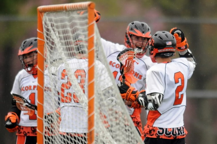 Oakland Mills's Evan Riss, second from right, celebrates his opening goal with teammates during a boys lacrosse game against Howard at Oakland Mills High School. (Brian Krista/BSMG).