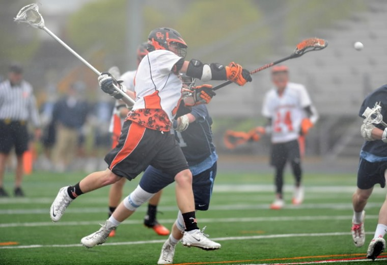 Oakland Mills's Wyatt Neely fires a shot towards the goal during a boys lacrosse game against Howard at Oakland Mills High School in Columbia. (Brian Krista/BSMG)
