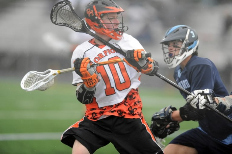 Oakland Mills's Thomas Brumbaugh feels the pressure by a Howard defenseman's stick during a boys lacrosse game at Oakland Mills High School in Columbia on Monday, April 28. (Brian Krista/BSMG)