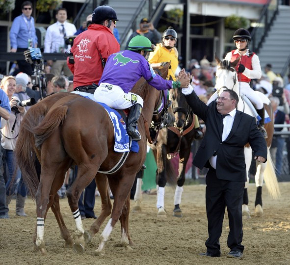California Chrome jockey Victor Espinoza hi-fives assistant trainer Alan Sherman as they head to winner's circle after winning The Preakness Stakes. (Kenneth K. Lam/Baltimore Sun)