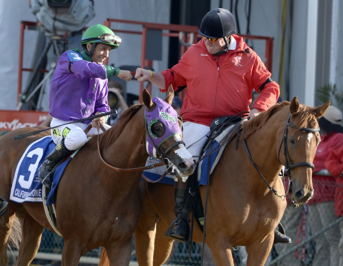 California Chrome jockey Victor Espinoza fist-bumps the out-rider as they head to Winner's Circle after winning The Preakness Stakes. (Kenneth K. Lam/Baltimore Sun)
