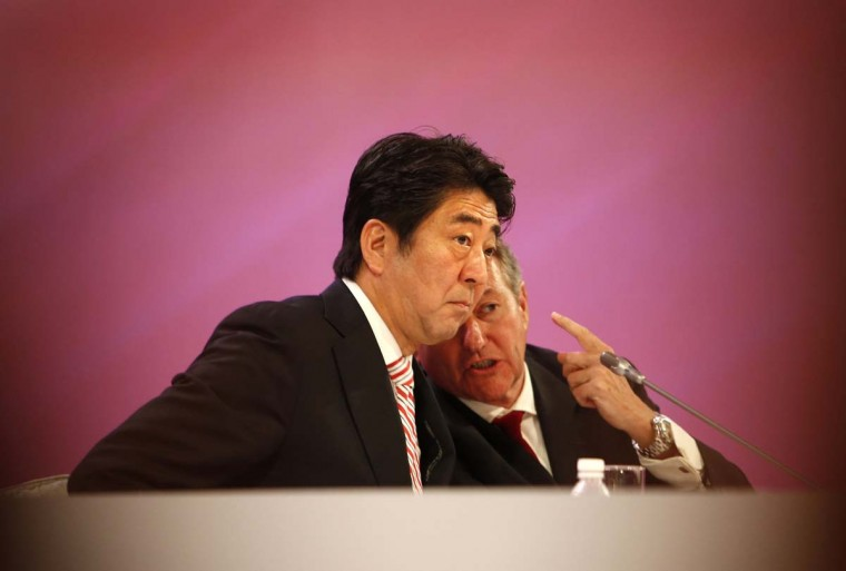 Japan's Prime Minister Shinzo Abe (L) listens to John Chipman, Director-General and Chief Executive of The International Institute for Strategic Studies (IISS), at the 13th IISS Asia Security Summit: The Shangri-La Dialogue, in Singapore May 30.  || PHOTO CREDIT: EDGAR SU  - REUTERS