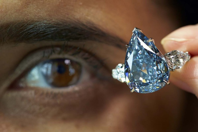 "A staff member poses with ""The Blue"" diamond during an auction preview for Christie's in Geneva May 9. The largest flawless vivid blue diamond in the world, weighing 13.22 carats, is expected to reach between CHF 19,000,000 and 23,000,000 (USD 21,000,000 to 25,000,000) when it goes on sale at an upcoming Magnificent Jewels sale in Geneva May 14.  