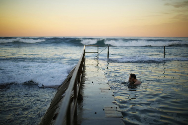 A swimmer splashes his face in between laps at a pool as the waves of the Pacific Ocean roll in during twilight at Sydney's South Cronulla Beach, May 5, 2014. Despite the sun setting earlier with a southern hemisphere winter approaching, Sydneysiders continue to take advantage of mild sea temperatures into May. (Jason Reed/Reuters)