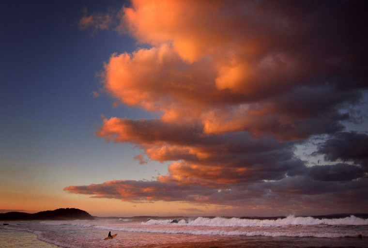 A surfer holding her board wades through the surf as clouds above are lit by the setting sun at Mollymook Beach on the south coast of New South Wales May 8, 2014. (REUTERS/David Gray)