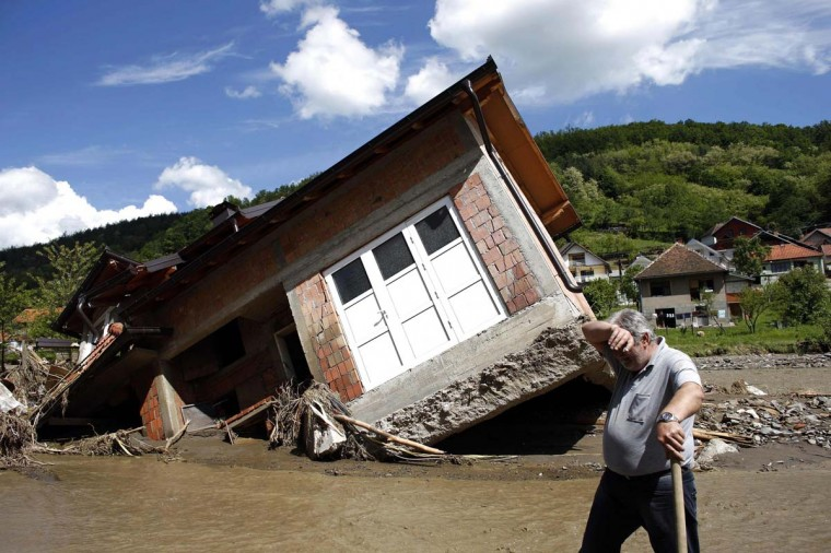 A man reacts near a house tilted by floods in the village of Krupanj, west from Belgrade, May 19, 2014. Communities in Serbia and Bosnia battled to protect towns and power plants on Monday from rising flood waters and landslides that have devastated swathes of both countries and killed dozens of people. (Marko Djurica/Reuters)