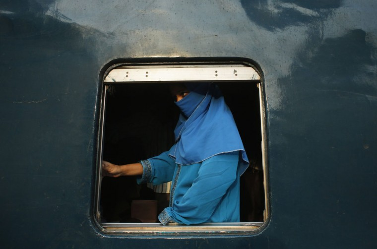 A veiled woman stands inside a compartment as the train approaches a station in Dhaka May 29, 2014. According to Bangladesh Railway, it carries about two hundred fifty thousands passengers every day from 456 railway stations using 334 trains in its countrywide network. REUTERS/Andrew Biraj