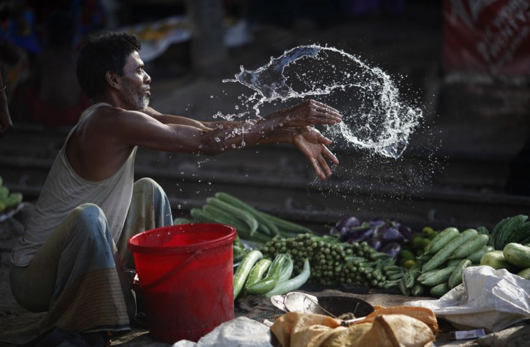 A vendor splashes water as he sells vegetable next to a railway track in Dhaka May 29, 2014. Bangladesh's economic growth this financial year, is expected to be slower than the 6 percent in 2012/13, after the country was gripped by political turmoil leading up to an election in January. REUTERS/Andrew Biraj