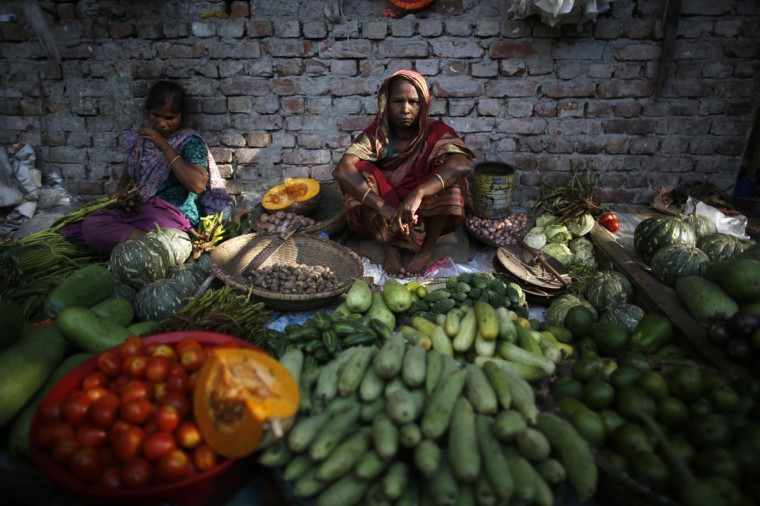 A woman sells vegetable under an overpass in Dhaka May 29, 2014. Bangladesh's economic growth this financial year, is expected to be slower than the 6 percent in 2012/13, after the country was gripped by political turmoil leading up to an election in January. REUTERS/Andrew Biraj