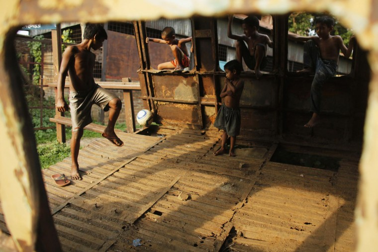 Children play football inside an abandoned train compartment next to a railway track in Dhaka May 29, 2014. Although Bangladesh's football team is positioned 162 in the FIFA ranking, the country has millions of football fans, most supporting the national football teams of Argentina and Brazil. REUTERS/Andrew Biraj