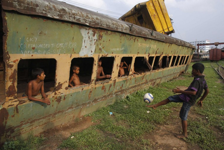 Children play football in front of an abandoned train compartment next to a railway track in Dhaka May 29, 2014. Although Bangladesh's football team is positioned 162 in the FIFA ranking, the country has millions of football fans, most supporting the national football teams of Argentina and Brazil. REUTERS/Andrew Biraj