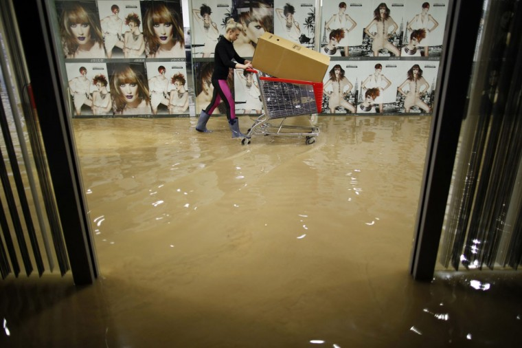 A woman pushes a trolley as she evacuates a hair salon in a shopping centre during flooding in the central Bosnian town of Zenica May 15, 2014. Several Bosnian cities have been affected by floods caused by heavy rains. (REUTERS/Dado Ruvic)