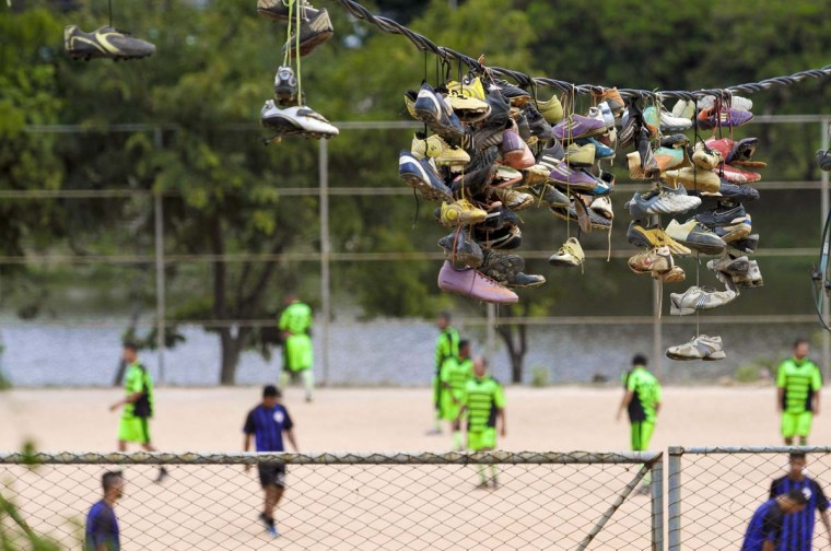 """Discarded soccer boots hang from an electric wire where they were thrown by their owners over several months after Sunday """"pelada"""" soccer matches in the Morro do Papagaio favela in Belo Horizonte, a World Cup host city, May 4, 2014. Sunday soccer is a decades-old tradition when Brazilians of all walks of life play on the beaches, in the slums, and on the streets matches that are known as """"peladas"""" or """"naked"""". Pelada can refer to a street match where everyone plays barefoot with """"naked"""" feet, or a match on a grassless """"naked"""" field, or a match with a ball so worn that it is """"naked"""". With the 2014 World Cup just one month away, people of all walks of life in the host cities are spending their Sundays practicing the sport for which their country is about to become the global stage. The tournament will take place in Brasilia, Belo Horizonte, Rio de Janeiro, Sao Paulo, Natal, Fortaleza, Salvador, Porto Alegre, Curitiba, Cuiaba, Manaus, and Recife. Picture taken May 4, 2014. (Washington Alves/Reuters)"""