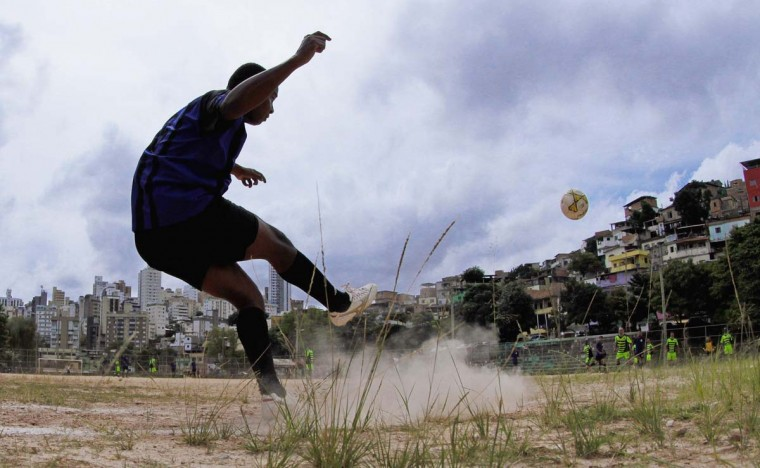 """A player takes a corner kick during a Sunday """"pelada"""" soccer match in the Morro do Papagaio favela in Belo Horizonte, a World Cup host city, May 4, 2014. Sunday soccer is a decades-old tradition when Brazilians of all walks of life play on the beaches, in the slums, and on the streets matches that are known as """"peladas"""" or """"naked"""". Pelada can refer to a street match where everyone plays barefoot with """"naked"""" feet, or a match on a grassless """"naked"""" field, or a match with a ball so worn that it is """"naked"""". With the 2014 World Cup just one month away, people of all walks of life in the host cities are spending their Sundays practicing the sport for which their country is about to become the global stage. The tournament will take place in Brasilia, Belo Horizonte, Rio de Janeiro, Sao Paulo, Natal, Fortaleza, Salvador, Porto Alegre, Curitiba, Cuiaba, Manaus, and Recife. Picture taken May 4, 2014. (Washington Alves/Reuters)"""