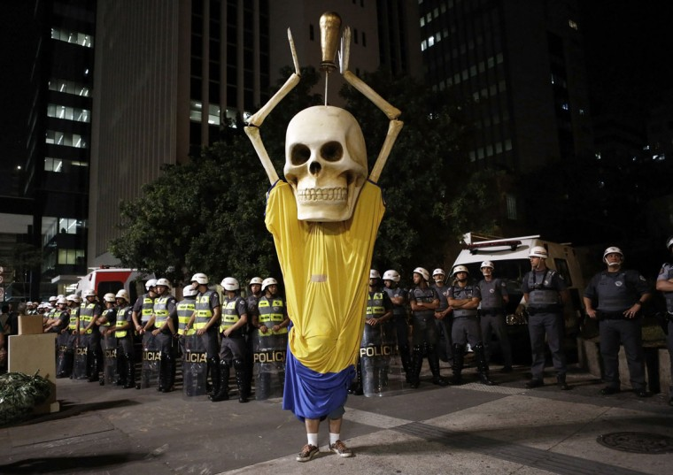 Military policemen stand in a line behind a demonstrator wearing the figure of a skeleton holding up a trophy representing that of the FIFA World Cup during a protest against the 2014 World Cup, in Sao Paulo May, 15 2014. Road blocks and marches hit Brazilian cities on Thursday as disparate groups criticized spending on the upcoming World Cup soccer tournament and sought to revive a call for better public services that swept the country last June. (REUTERS/Nacho Doce)