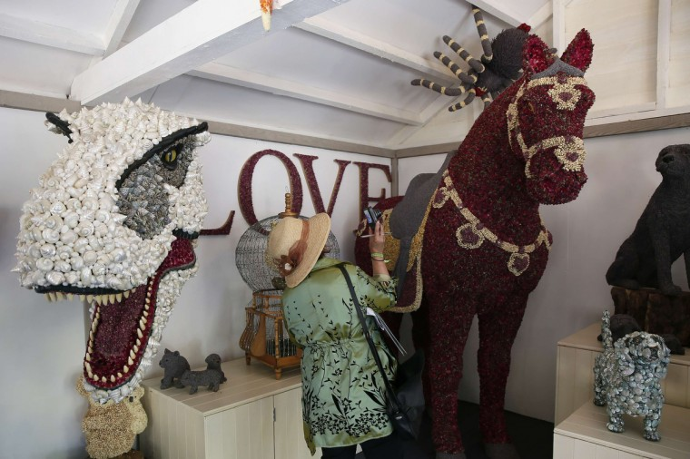 A woman takes a photograph of animals made from shells during media day at the Chelsea Flower Show in London May 19, 2014. (Stefan Wermuth/Reuters)