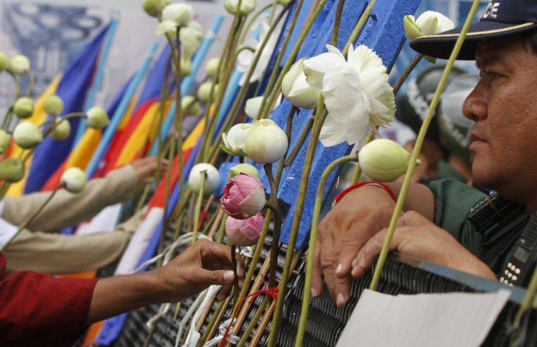 A Buddhist monk and protesters put lotus flowers on a barricade set up by police officers during a demonstration near the Phnom Penh Municipal Court in central Phnom Penh. The protesters demanded the release of 23 detainees who have been jailed since January 3, when military police opened fire on workers striking over low pay, killing four people. (Samrang Pring/Reuters)