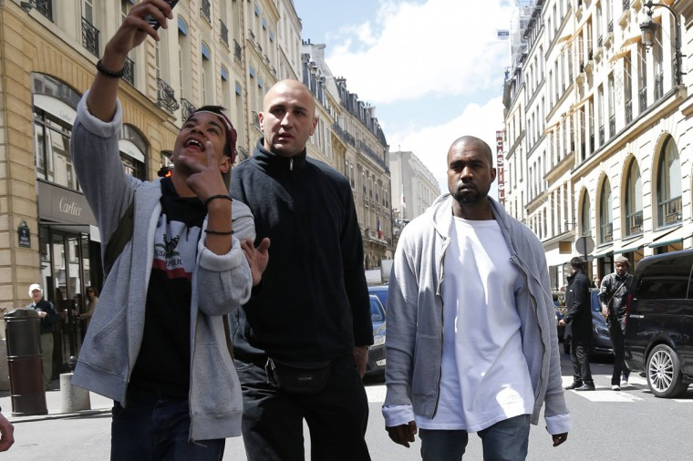 A fan takes pictures as rapper Kanye West arrives at a fashion designer shop in Paris May 22, 2014. U.S. television personality Kim Kardashian and rapper Kanye West will celebrate their wedding in Florence on May 25, an official from the mayor's office confirmed on Friday. REUTERS/Gonzalo Fuentes